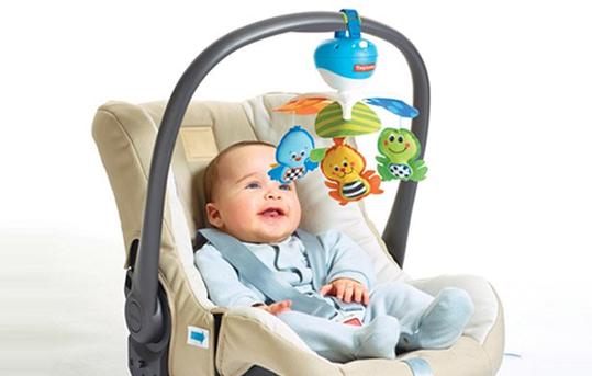 Baby in Babyschale mit Hängespielzeug.